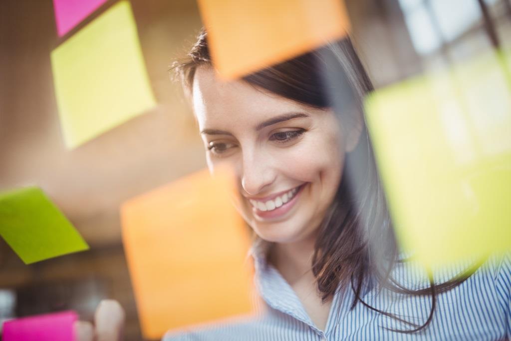 glückliche Frau vor Notizzetteln